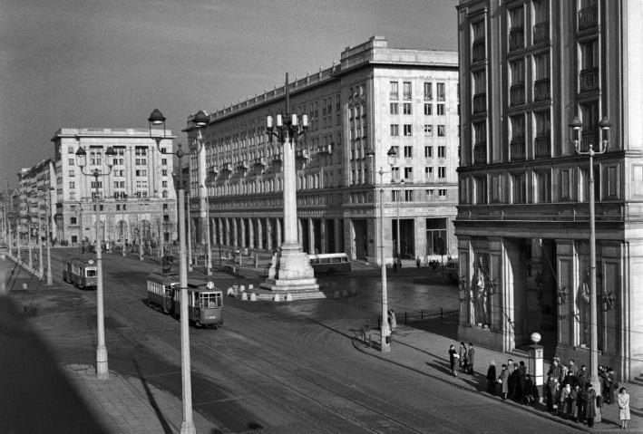 Warszawa, 1954. MDM – plac Konstytucji, ulica Marsza³kowska. Fot. Zbyszko Siemaszko/FORUM Plac Konstytucji w 1954 r. Jest sercem Marsza³kowskiej Dzielnicy Mieszkaniowej. Otwarto go 22 lipca 1952 r. Poœrodku placu stanê³a wówczas trybuna, z której Boles³aw Bierut przyjmowa³ manifestacjê. Plac otaczaj¹ potê¿ne budynki z podcieniami i wielkimi sklepami. Zbudowano je z rozmachem. Plejada artystów i rzemieœlników ozdobi³a budowle socrealistycznymi rzeŸbami, mozaikami, kutymi w metalu bramami, malowid³ami, a nawet ceramik¹. By³a to najbardziej reprezentacyjna dzielnica mieszkaniowa w ca³ej Polsce.